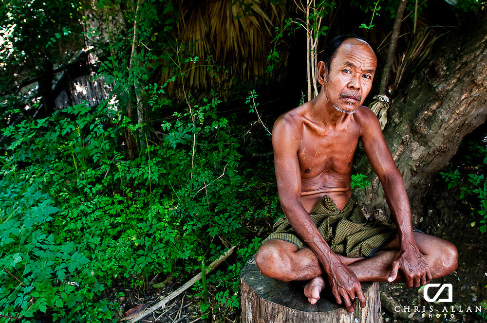A Burmese potter sits for a portrait. He lived on the edge of the Ayerwaddy River where he regarded tourists that visited under the watchful eye of tour operators with a stern glare.