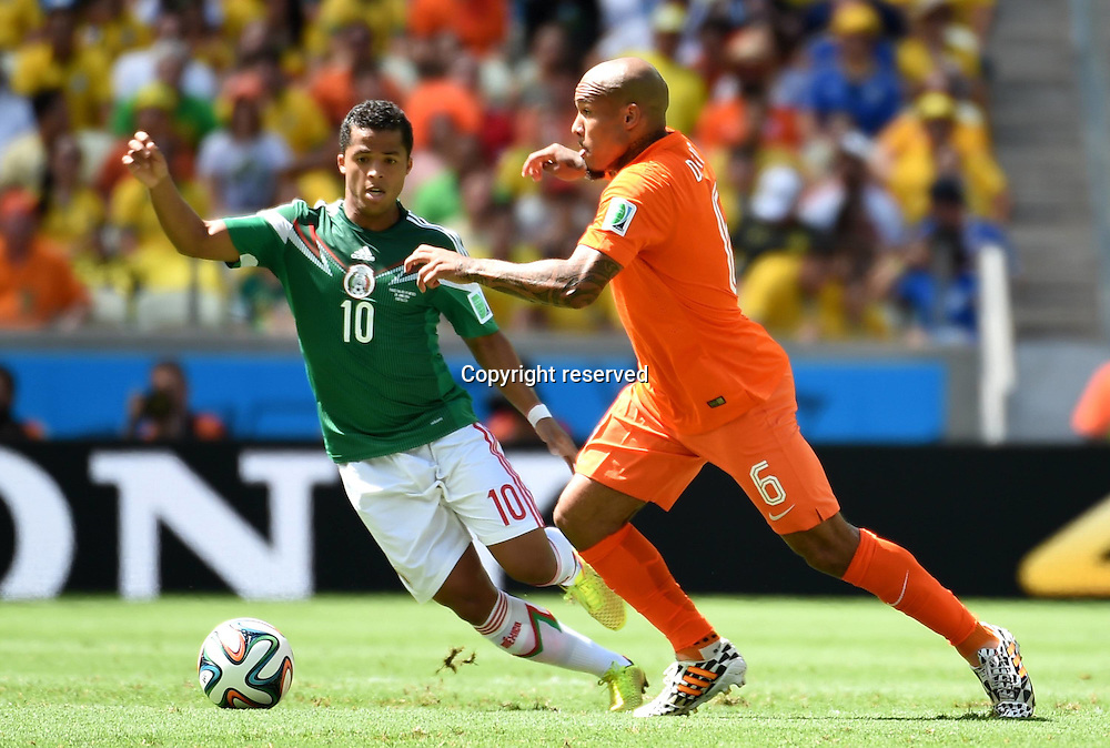29.06.2014. Fortaleza, Brazil. Netherlands Nigel de Jong (R) challenges Mexicos Giovani dos Santos during a Round of 16 match between Netherlands and Mexico of 2014 FIFA World Cup at the Estadio Castelao Stadium in Fortaleza, Brazil, on June 29, 2014.