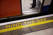 A classic Mind the Gap painted sign on a London Underground platform.