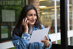 "© Licensed to London News Pictures. 15/08/2016. Sutton Coldfield, West Midlands,UK. Bishops Vesey's Grammar School pupils celebrating their A level results. Pictured, Sofia Kaur, 18, rings her parents to tell them the good news. Headmaster Dominic Robson said, ""The pupils had done amazingly well, achieving 80% A star and B grades especially given the change to the marking of the A level system this year. Photo credit: Dave Warren/LNP"