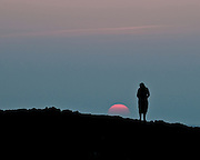 A woman looks down at the setting sun on the Big Island of Hawaii.