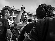 """07 MARCH 2015 - NAKHON CHAI SI, NAKHON PATHOM, THAILAND: Volunteers bring a man out of a trance after he charged the stage at the Wat Bang Phra tattoo festival. Wat Bang Phra is the best known """"Sak Yant"""" tattoo temple in Thailand. It's located in Nakhon Pathom province, about 40 miles from Bangkok. The tattoos are given with hollow stainless steel needles and are thought to possess magical powers of protection. The tattoos, which are given by Buddhist monks, are popular with soldiers, policeman and gangsters, people who generally live in harm's way. The tattoo must be activated to remain powerful and the annual Wai Khru Ceremony (tattoo festival) at the temple draws thousands of devotees who come to the temple to activate or renew the tattoos. People go into trance like states and then assume the personality of their tattoo, so people with tiger tattoos assume the personality of a tiger, people with monkey tattoos take on the personality of a monkey and so on. In recent years the tattoo festival has become popular with tourists who make the trip to Nakorn Pathom province to see a side of """"exotic"""" Thailand.   PHOTO BY JACK KURTZ"""