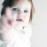 Young girl age 2-5 years old wearing white with blue eyes