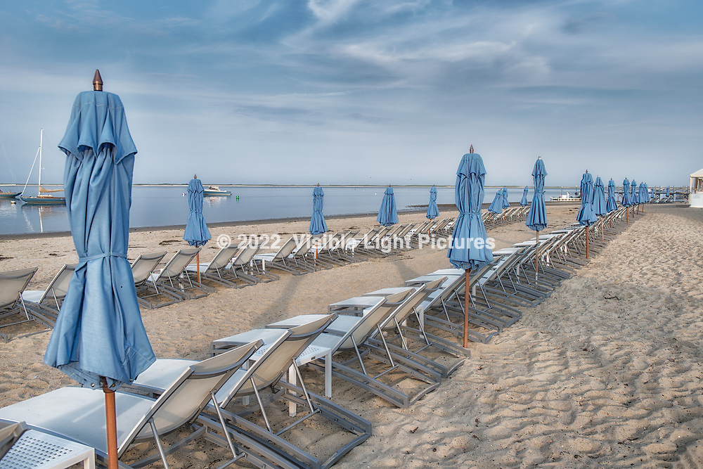 Blue beach umbrellas along the shoreline in Chatham, Massachusetts, Cape Cod.