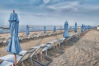 Blue beach umbrellas along the shoreline in Chatham, Massachusetts, Cape Cod.
