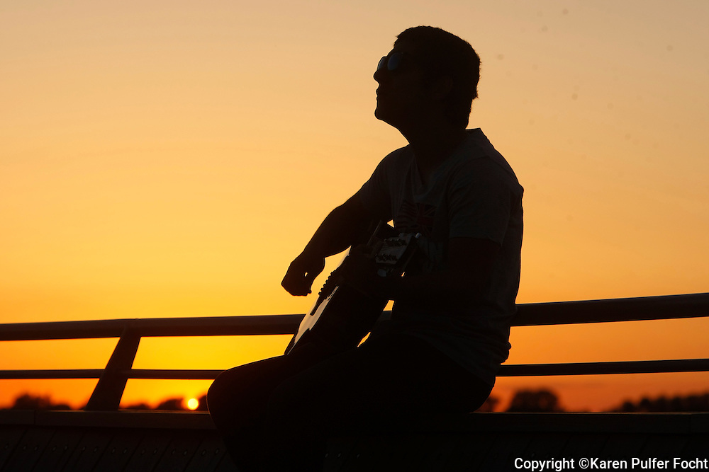 A visitor to Memphis plays his guitar, at sunset, in the new park at Beale Street Landing in downtown Memphis. Scenes from downtown Memphis, Tennessee.