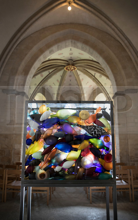 © Licensed to London News Pictures. 24/05/2018. Canterbury, UK. Artists Baldwin & Guggisberg's installation 'Yesterday, Today, Tomorrow' is displayed in The Crypt at Canterbury Cathedral. A series of glass installations by artists Philip Baldwin and Monica Guggisberg reflecting on themes of war and remembrance, migration and refugees are going on display at the cathedral commemorating the 100th anniversary of the end of the First World War. Under an Equal Sky will take visitors on a journey that begins with the Boat of Remembrance in the Nave and ends with a glass wall of multi-coloured vessels in The Crypt . Photo credit: Peter Macdiarmid/LNP