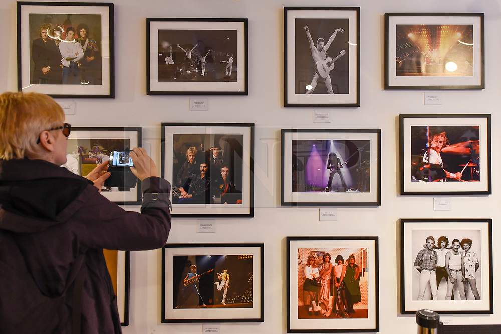 "© Licensed to London News Pictures. 18/10/2018. LONDON, UK. A visitor views Queen photographs on display in the Queen pop-up shop which has opened in Carnaby Street.  Coinciding with the release next week of the movie ""Bohemian Rhapsody"", the shop offers Queen music fans memorabilia, a display of stage costumes as well as archived Queen performance footage.  Photo credit: Stephen Chung/LNP"