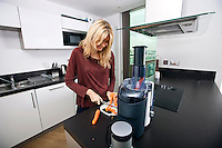 Young blond woman chopping carrots on cutting board in kitchen