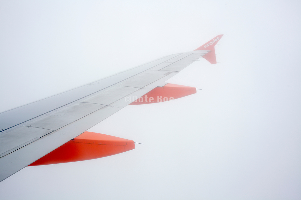 passenger airplane wing while flying through heavy fog
