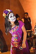 A young Mexican girl wearing skeleton face paint during the Dead of the Dead festival in San Miguel de Allende, Mexico. The multi-day festival is to remember friends and family members who have died using calaveras, aztec marigolds, alfeniques, papel picado and the favorite foods and beverages of the departed.