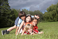 Portrait of five children (7-9) lying on top of each other in meadow