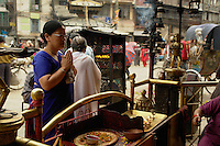 Devout Hindu woman preys at a shrine in Indra Chawk Square of Kathmandu, Nepal.
