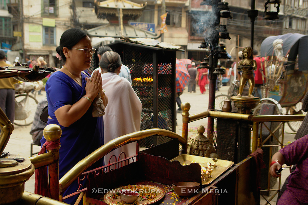 Devout Hindu woman preys at a shrine in Indra Chawk Square of Kathmandu, Nepal.