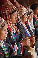 Akha hilltribe women wearing ornate headress performing traditional Akha dance, northern Thailand near Chiang Rai.