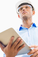 Low angle view of male architect holding tablet PC against sky