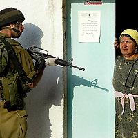 An elderly Palestinian woman stand beside the door of a local hospital as Israeli troops clash with Palestinian youths in the West Bank village of Salfit July 15, 2005. Israeli helicopters pounded targets in Gaza on Friday after a deadly Palestinian rocket attack that sparked fierce internal fighting between militants and Palestinian police trying to stop further barrages..PHOTO BY Olivier Fitoussi / BauBau.