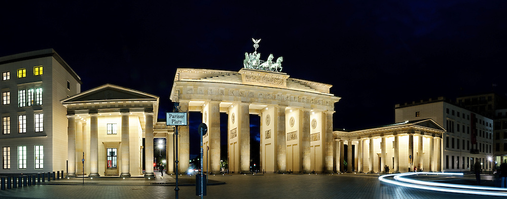 Panoramic shot of the Brandenberg Gate at night, with the Pariser Platz sign at left and light streaks from the headlights of passing cars at right. On top of the gate is the Quadriga, a depiction of Victoria, the Roman goddess of victory being carried in a chariot drawn by four horses.