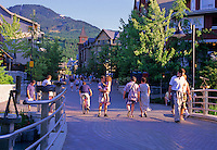 A family walks across the Village park bridge in Whistler Village on a summer evening.