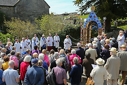 © Licensed to London News Pictures. 05/05/2016. Tissington, UK. A crowd watches as members of the local church bless one of six colourful dressed wells in the Derbyshire village of Tissington. The origins of well dressing may have pagan roots later given a Christian Meaning. The dressings are made of clay dug locally which is adorned with dried flowers. The dressings are erected on the eve of Ascension day ready for the ceremony of blessing. Photo credit : Ian Hinchliffe/LNP
