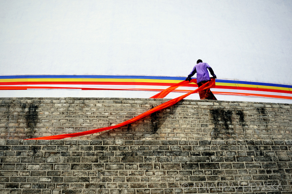 Sri Lanka, Anuradhapura. Man putting the red ribbon on the temple's walls.