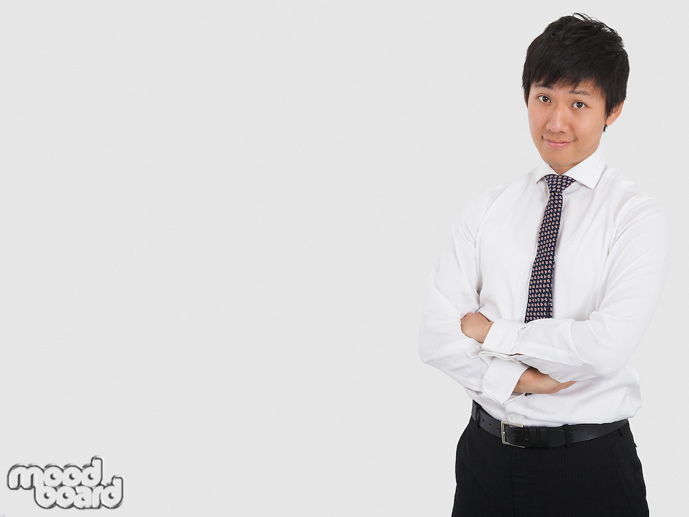 Portrait of confident businessman with arms crossed standing over white background
