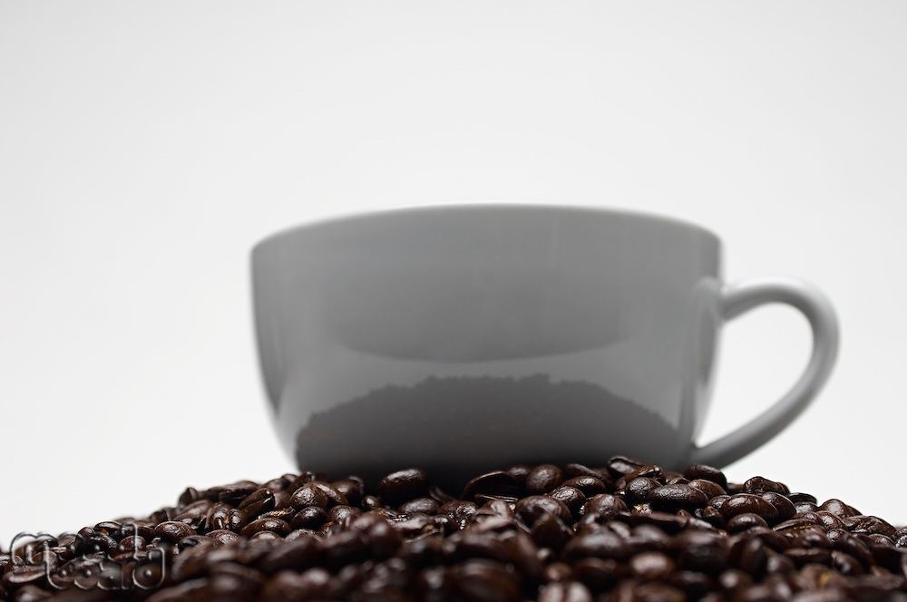 Cup of coffee on heap of coffee beans