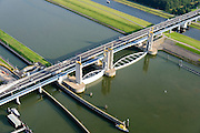 Nederland, Zuid-Holland, Botlek, 28-09-2014; Functioneringssluiting Hartelkering. De waterkering in het Hartelkanaal wordt een maal per jaar, voordat het stormseizoen begint, getest. Tijdens het sluiten van de kering ligt alle scheepvaartverkeer naar de Rotterdamse haven stil.<br /> De kering, onderdeel van de Deltawerken, vormt samen met de Maeslantkering de Europoortkering en beschermt Rotterdam en achterland bij extreme waterstanden.<br /> Port of Rotterdam. Aerial view of one of the two storm surge barriers. This barrier, the Hartelkering in the Hartel canal, is tested once a year together with the greater nearby Maeslant barrier (in the New Waterwy), <br /> During the so-called functioning closure, taking place one a year before the storm season begins, the waterway and canal, leading to the Port of Rotterdam, are closed.<br /> luchtfoto (toeslag op standard tarieven);<br /> aerial photo (additional fee required);<br /> copyright foto/photo Siebe Swart