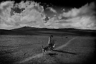 """Chimborazo Volcano (6,268 metres [20,564 ft]) peeks through a break in the clouds above a Kichwa herder returning to her high settlement at 4,100 m (13,451ft) on the desert-like """"el arenal"""" from the crossroads to where her family raises sheep and alpaca.  Ecuador."""