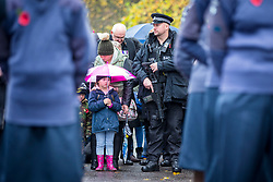 © Licensed to London News Pictures. 11/11/2018. Doncaster UK. An armed Police officer stands next to a little girl at the Service of remembrance at the Cenotaph in Doncaster to mark the 100th anniversary of the end of the First World War. Photo credit: Andrew McCaren/LNP