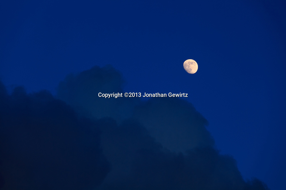 A bright, waxing, sharp-featured  moon contrasts with dark, puffy clouds and the dark blue sky in a dreamscape image. WATERMARKS WILL NOT APPEAR ON PRINTS OR LICENSED IMAGES.