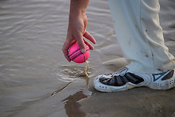 © Licensed to London News Pictures. 24/08/2017. Solent, UK. A fielder picks the ball out of the sea water. Teams take part in the Brambles Bank Cricket Match in the middle of The Solent strait on August 24, 2017. The annual cricket match between the Royal Southern Yacht Club and The Island Sailing Club, takes place on a sandbank which appears for 30 minutes at lowest tide. The game lasts until the tide returns. Photo credit: Ben Cawthra/LNP