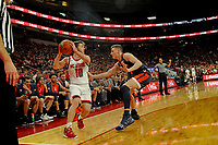 Wolfpack guard Braxton Beverly (10) looks to pass around a UVA defender during ACC action in PNC Arena.