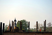 The ruins of Wat Mahathat, or  'temple of the great relic', built from laterite and surrounded by a moat.