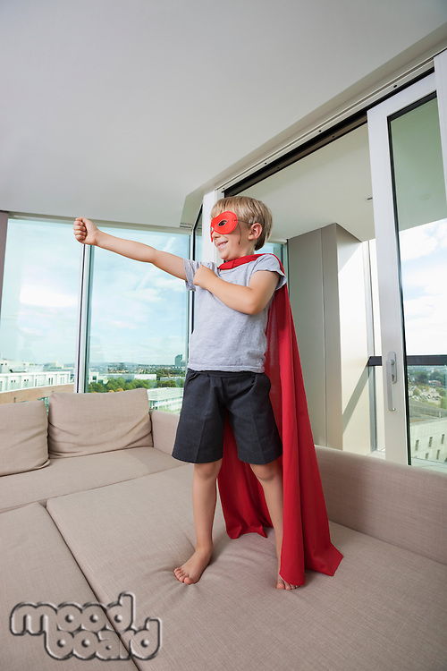 Smiling boy in super hero costume standing with arm outstretched on sofa bed at home