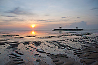 Sun rising on ridges in the sand at Sanur beach at low tide in Bali, Indonesia