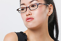 Close-up of young Chinese woman wearing glasses over white background