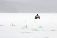 A fisherman drives an ATV across a frozen lake to check his fishing lines.