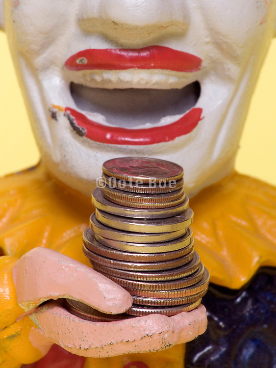 clown doll figure coin bank bringing money to his mouth
