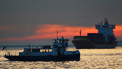 © Licensed to London News Pictures. 13/04/2016. Sunrise seen this morning over the Thames at Gravesend in Kent. Container ship OPDR LISBOA seen heading towards Tilbury as the ferry crosses the river from Essex to Kent. Credit : Rob Powell/LNP