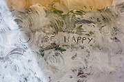 The optimistic words Be Happy with two smiley faces drawn on a whitewashed shop window, a victim of the UK recession.