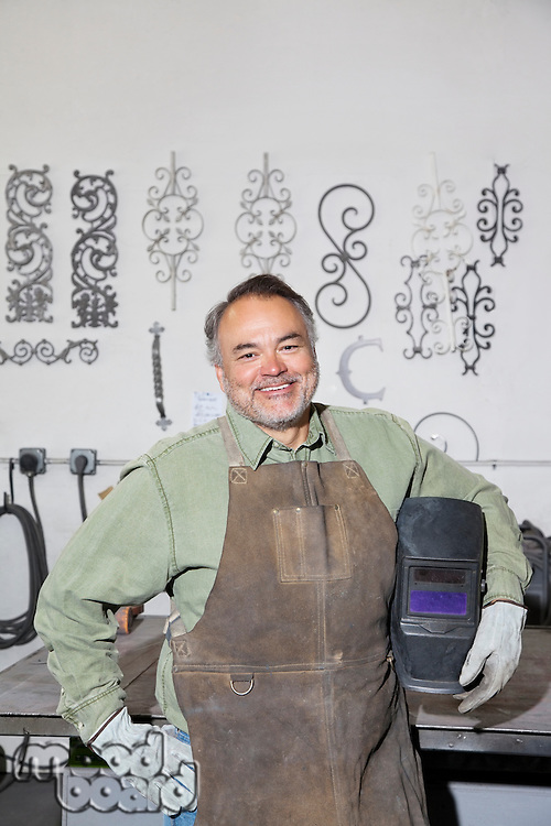 Portrait of a happy mature metalworker holding protective mask in workshop