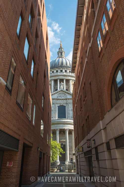 Partial view of the dome of St Paul's Cathedral, one of the most distinctive of London's landmarks, flanked by two modern office buildings. There has been a church on this site since 604 AD. The current building, with it's massive dome, was designed by Christopher Wren and dates back to the late 17th century.