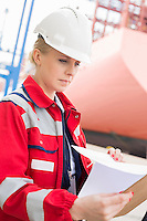 Female engineer reading documents in shipping yard
