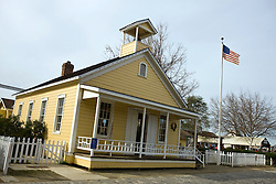 Exterior of old schoolhouse, painted yellow with white picket fence and American flag, Old Sacramento, California, United States of America