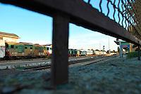 Le Ferrovie del Sud Est nascono in Puglia, nell'ottobre del 1931. A questà nuova società veniva dato in concessione l'insieme delle reti ferroviarie precedentemente gestite da diversi organismi (Società per le Ferrovie Salentine, Società per le Ferrovie Sussidiate, Ferrovie dello Stato)..Le aree pugliesi attraversate dalla società ferroviaria sono l'area barese, la fascia Taranto-Brindisi e l'area leccese-salentina, collegando fra loro i capoluoghi di Bari, Taranto e Lecce, nonché oltre 130 comuni delle province meridionali..Il reportage fotografico sulle Ferrovie Sud Est intende testimoniare l'evoluzione tecnologica che, durante gli anni, ha modificato e migliorato il servizio ferroviario e la convivenza del progresso con tracce del passato, attraverso un viaggio tra le stazioni e i depositi..Stazione di Mungivacca, fotografata attraverso le grata di recinzione.