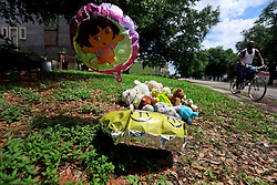29 May 2014. New Orleans, Louisiana.<br /> A roadside memorial at the corner of N. Rocheblave and Franklin Ave. The memorial is for a dog killed in the street 2 weeks earlier. A neighbor confirmed it was a stray that used to walk people to church on Sunday. A local woman asked the home owner if she could place the memorial outside his house.  Less than a block away a 17 year old male was shot and killed May 26th. There is no memorial for the teenager - only for the dog.<br /> Charlie Varley/varleypix.com
