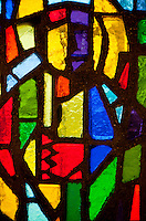 Vibrant, colorful, stained glass window seen in a cemetery in Provence, France.