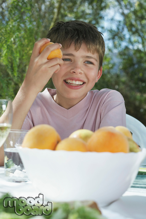 Portrait of boy (10-12) eating peach at garden table smiling