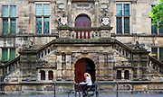 Girl on bicycle passing the historic Stadhuis building, Leiden, Netherlands. The old Renaissance exterior dates from 1595